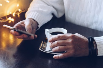 Mid section of man using smartphone while having coffee