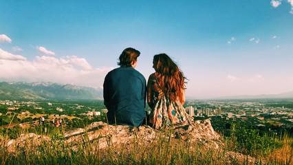Rear view of couple sitting on mountain