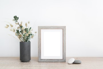 Blank picture frame with flower vase and pebbles on table