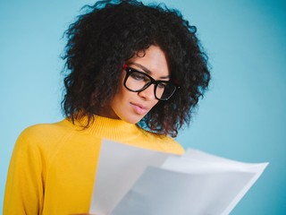 Young woman reading documents while standing against blue background