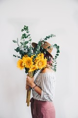 Side view of woman holding flower bouquet while standing against white background