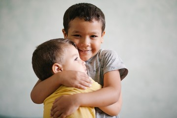 Smiling brothers embracing each other