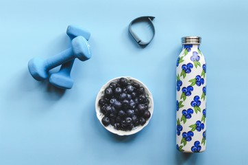 Overhead view of water bottle, blueberries, dumbbell and fitness tracker on blue background