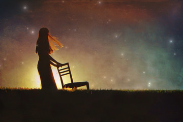 Woman holding a chair while standing in the field against the starry sky