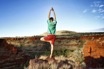 Rear view of man standing in tree pose at Karijini National Park