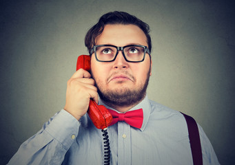 Confused man speaking on phone
