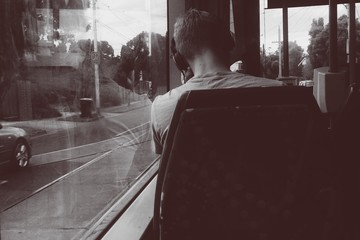 Rear view of man listening to music while traveling in bus