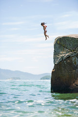 Girl diving into sea from rock