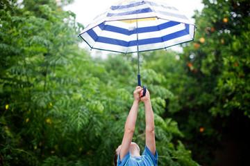 Boy playing with umbrella in rain