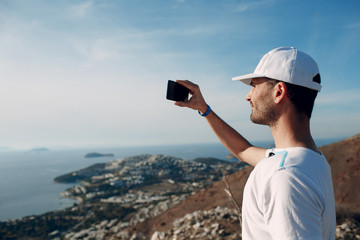 Climber on top photographing the landscape on a smartphone
