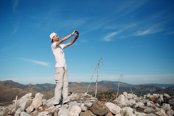 Climber on top photographing the landscape on a mobile phone