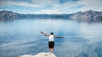 Rear view of man jumping in lake against mountains
