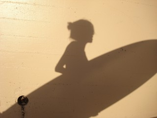 Shadow of woman holding surfboard