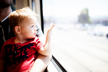 Baby boy looking out through train window while sitting with father