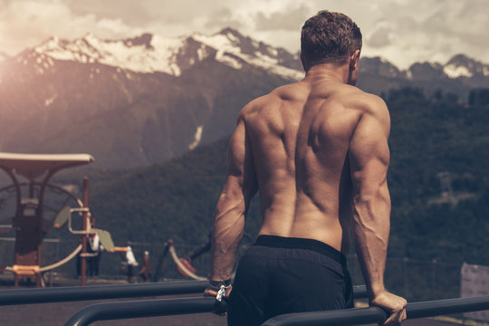 Rear view of a young athletic half naked man doing push ups on parallel bars outdoors. Fitness and exercising outdoors in nature highlands environment. Selective focus, close up.