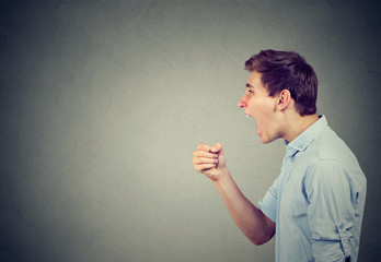 Screaming young man on gray background