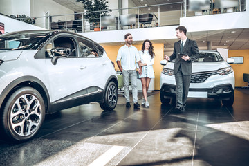 Sales manager helping young couple to choose a new car Wall mural
