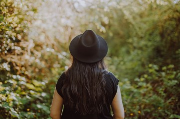 Rear view of woman in black hat standing in outdoors