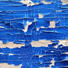 Close up of blue peeling off paint on white wall