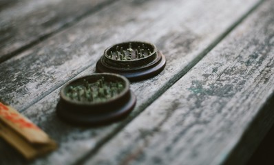 Close up of weed grinder with rolling papers on a wooden picnic table