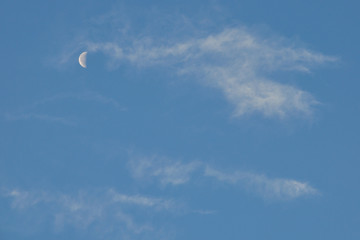 Crescent, half moon in the blue sky among the small bright clouds
