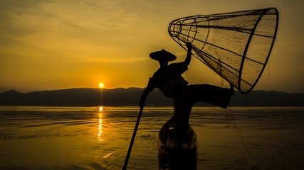 Sillhouette of fisherman with old net fishing in Inle Lake