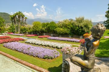 Panorama di un giardino fiorito con statua, aiuole colorate e palme, Villa Taranto, Lago Maggiore, Italia