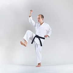 Active adult athlete doing formal karate exercises on gray background
