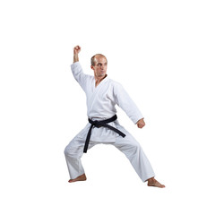 On a white background, an active athlete does formal karate exercises.