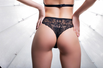 Girl in black lacy panties on a white background