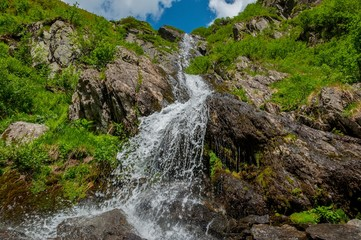 Close up mountain waterfall in Carpathians mountains. Sitting on the rock edge near faterfall and enjoying stunning  view.