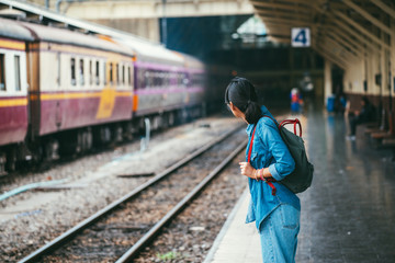Asian woman traveler waiting train on the platform of the railway station- travel and transportation concept