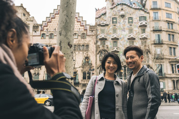 Asian tourist couple taking a picture with a camera