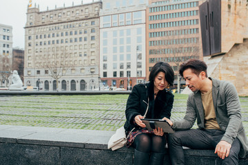 Asian tourist couple looking at the tablet
