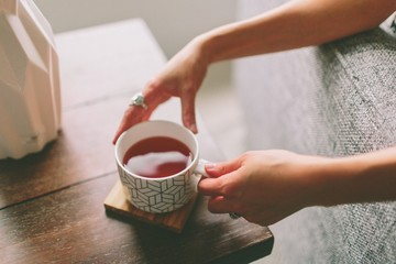 Woman's hand placing cup of tea