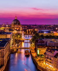 aerial view of Berlin skyline with Berlin Cathedral and Spree river in beautiful post sunset twilight during blue hour at dusk with dramatic colorful clouds , central Berlin Mitte, Germany