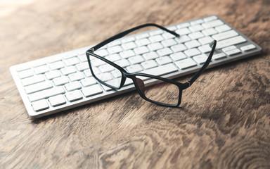 Eyeglasses on computer keyboard.