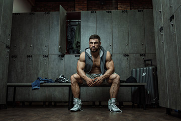 Bodybuilder sits tired in locker room after finishing training