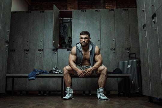 Bodybuilder sitting in locker room