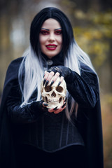 Image of witch girl in black cloak with skull