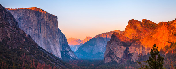 Yosemite National Park Tunnel View overlook at sunset. Front view panorama of popular El Capitan and Half Dome at deep red sunset. Summer american holidays. California, United States.