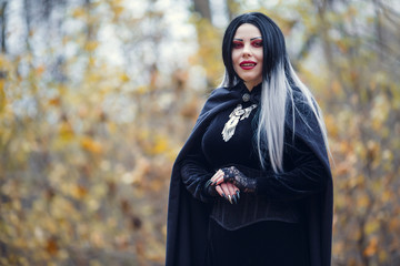 Photo of smiling female vampire in black cloak with amulet