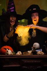 Photo of two witches in black hats making potion