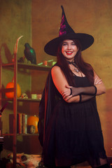 Portrait of witch in black dress and hat in magic room
