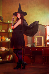 Full-length image of witch in black dress with developing raincoat and hat in magic room