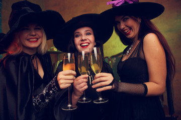 Photo of three young witches with glass of champagne