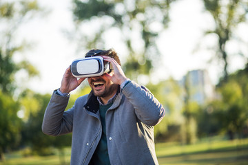 Businessman using vr headset in a park