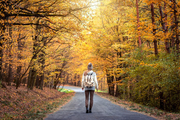 Woman walking on the road in the middle of forest at autumn