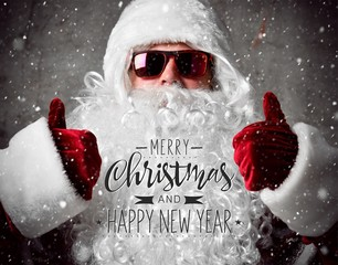 Santa Claus show thumbs up under snow confetti. New year and Merry Christmas