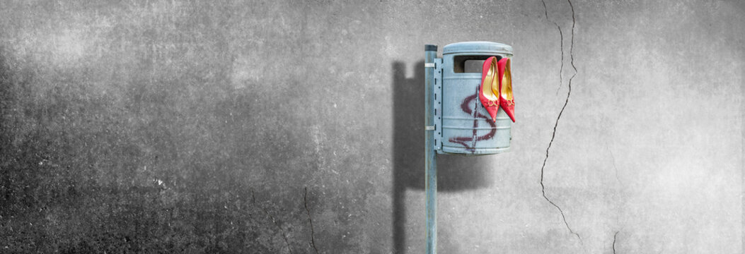 Geld macht nicht glücklich - Frau hat symbolhaft ihre roten Stöckelschuhe weggeschmissen und auf den Mülleimer ein Dollarzeichen gemalt